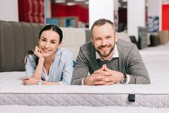 Portrait of smiling couple lying on mattress. In furniture store stock photos