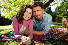 Portrait of smiling couple lying on picnic blanket in park Stock Image