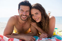 Portrait of smiling couple lying together on blanket at beach Stock Photography