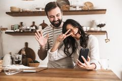 Portrait of smiling couple hugging together and holding smartphone while cooking in kitchen at home. Portrait of smiling couple men and women 30s wearing aprons royalty free stock photo
