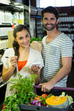 Portrait of smiling couple with notepad shopping for vegetables in organic section Royalty Free Stock Image