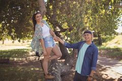 Portrait of smiling couple playing on tree trunk Royalty Free Stock Photo