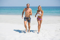 Portrait of smiling couple running at beach. On sunny day Royalty Free Stock Photography