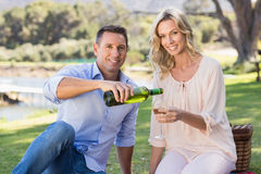 Portrait of smiling couple sitting and pouring wine in glass Royalty Free Stock Image