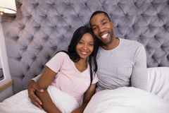 Portrait of smiling couple sitting together on bed Royalty Free Stock Image