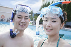 Portrait of smiling couple in snorkeling gear in the pool and looking at camera Stock Image