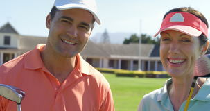 Portrait of smiling couple standing with golf club stock footage