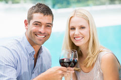 Portrait of smiling couple toasting red wine while sitting by swimming pool Royalty Free Stock Photography