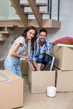 Portrait of smiling couple unpacking computer from cardboard box Stock Image