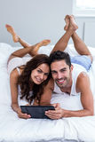 Portrait of smiling couple using digital tablet Stock Images