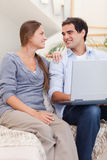 Portrait of a smiling couple using a laptop Stock Photo