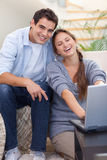 Portrait of a smiling couple using a notebook Stock Photos