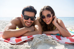 Portrait of smiling couple wearing sunglasses while lying together on blanket at beach Royalty Free Stock Images