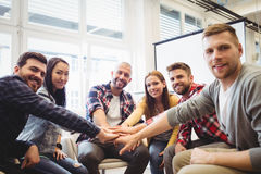 Portrait of smiling creative business people stacking hands. In meeting room at office Royalty Free Stock Photo