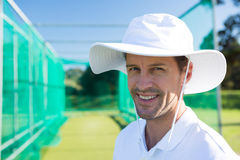 Portrait of smiling cricketer standing at field. On sunny day stock photography