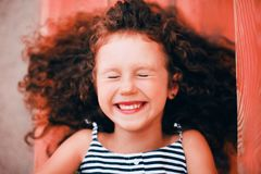 Portrait of smiling curly funny girl in Living Coral. Portrait of smiling curly funny girl outside. Authentic toddler in the city inspired by Living Coral royalty free stock photography