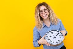 Woman in shirt with clocks. Portrait of smiling curly-haired woman in striped shirt and round eyeglasses isolated on orange background holding clocks time limit stock images