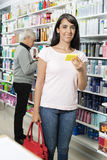 Portrait Of Smiling Customer Holding Product In Pharmacy Stock Photography