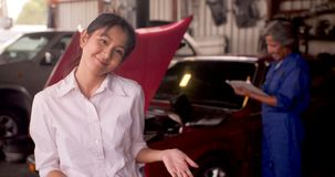 Portrait of smiling customer while a mechanic works on a car in the background. stock video