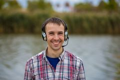 Portrait of a smiling customer service operator wearing a headset. Portrait of a handsome smiling customer service operator wearing a headset standing on river Stock Photos