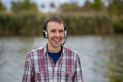 Portrait of a smiling customer service operator wearing a headset. Portrait of a handsome smiling customer service operator wearing a headset standing on river Stock Image