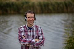 Portrait of a smiling customer service operator wearing a headset. Portrait of a handsome smiling customer service operator wearing a headset standing on river Stock Photo