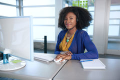 Portrait of a smiling customer service representative with an afro at the computer using headset Stock Photos