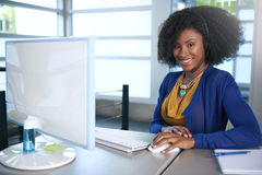 Portrait of a smiling customer service representative with an afro at the computer using headset Royalty Free Stock Photos