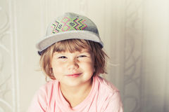 Portrait of smiling cute blond baby girl in gray cap Royalty Free Stock Images