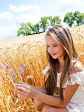 Portrait of smiling cute little girl child on field of wheat holding flowers royalty free stock photography