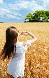 Portrait of smiling cute little girl child on field of wheat showing shape of heart stock image