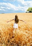 Portrait of smiling cute little girl child running through field of wheat royalty free stock photos