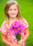 Portrait of a smiling cute little girl with flowers. Funny Stock Photos