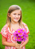 Portrait of a smiling cute little girl with flowers Stock Photo