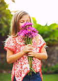 Portrait of a smiling cute little girl with flowers. Smelling Stock Images