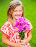 Portrait of a smiling cute little girl with flowers Royalty Free Stock Image