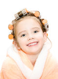 Portrait of smiling cute little girl in hair curlers and bathrob Royalty Free Stock Photography