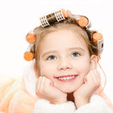 Portrait of smiling cute little girl in hair curlers Stock Photos