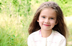 Portrait of smiling cute little girl in summer day. Outdoor Stock Photos