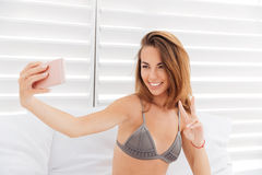 Portrait of a smiling cute woman in bikini making selfie Stock Photo