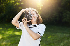 Portrait of smiling cute woman wearing white blouse taking photo with her retro camera while standing in green park or on meadow. Stock Images