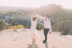 Portrait of smiling dancing wedding couple on the top hill, city and sky background Royalty Free Stock Photo