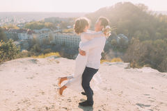 Portrait of smiling dancing wedding couple on the top hill, city and sky background Royalty Free Stock Photos