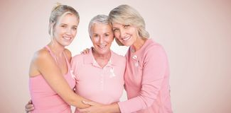 Composite image of portrait of smiling daughters with mother supporting breast cancer awareness Stock Image