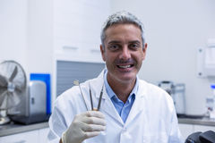 Portrait of smiling dentist holding dental tools Royalty Free Stock Images