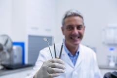 Portrait of smiling dentist holding dental tools Stock Image