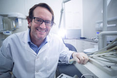 Portrait of smiling dentist sitting on chair Royalty Free Stock Image