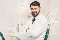 Portrait of smiling dentist. Dentist at workplace. Cheerful bearded doctor sitting in spacious modern office and looking at camera with smiling kind heartedly royalty free stock photo