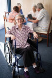 Portrait of smiling disabled senior woman sitting on wheelchair against friends Stock Image