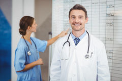 Portrait of smiling doctor with colleague pointing at chart Royalty Free Stock Photography